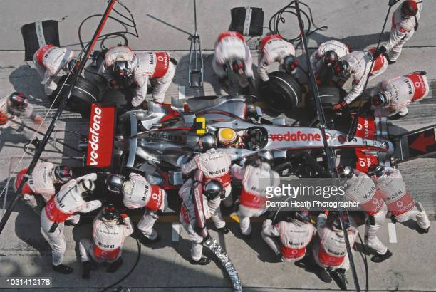 Lewis Hamilton of Great Britain driver of the Vodafone McLaren Mercedes McLaren MP4-22 Mercedes V8 is surrounded by mechanics as he makes a pit stop...