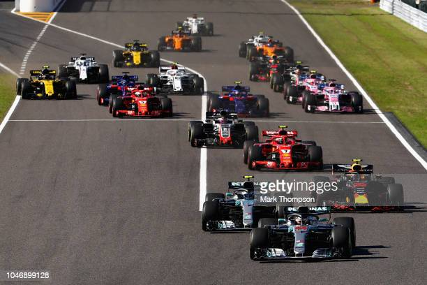 Lewis Hamilton of Great Britain driving the Mercedes AMG Petronas F1 Team Mercedes WO9 leads the field into turn one at the start during the Formula...