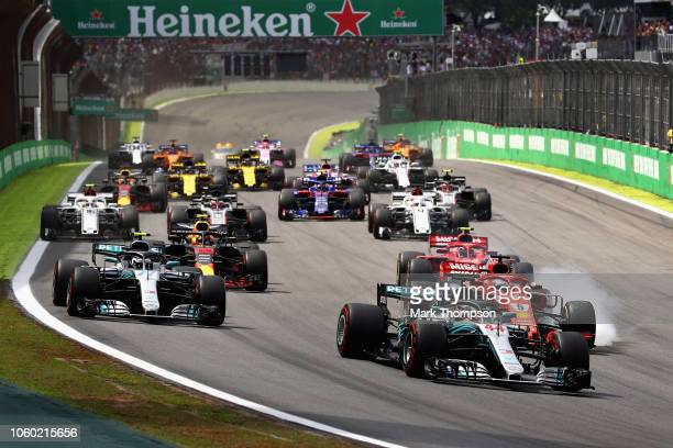 Lewis Hamilton of Great Britain driving the Mercedes AMG Petronas F1 Team Mercedes WO9 leads the field as Sebastian Vettel of Germany driving the...