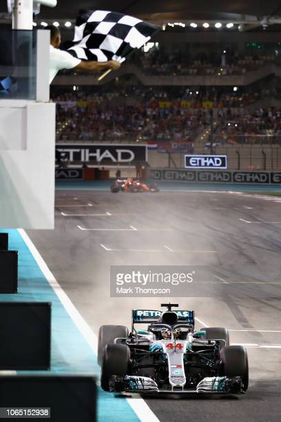 Lewis Hamilton of Great Britain driving the Mercedes AMG Petronas F1 Team Mercedes WO9 takes the chequered flag and the win during the Abu Dhabi...