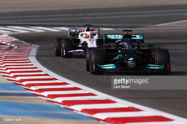 Lewis Hamilton of Great Britain driving the Mercedes AMG Petronas F1 Team Mercedes W12 leads Nikita Mazepin of Russia driving the Haas F1 Team VF-21...