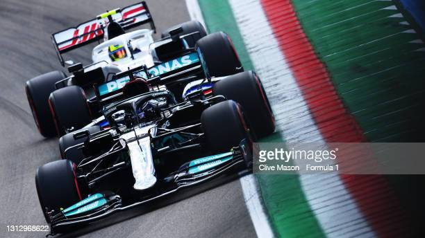 Lewis Hamilton of Great Britain driving the Mercedes AMG Petronas F1 Team Mercedes W12 leads Mick Schumacher of Germany driving the Haas F1 Team...