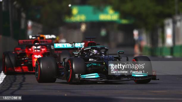 Lewis Hamilton of Great Britain driving the Mercedes AMG Petronas F1 Team Mercedes W12 leads Charles Leclerc of Monaco driving the Scuderia Ferrari...