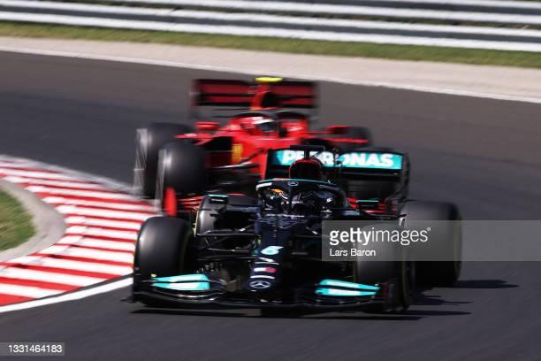 Lewis Hamilton of Great Britain driving the Mercedes AMG Petronas F1 Team Mercedes W12 leads Carlos Sainz of Spain driving the Scuderia Ferrari SF21...