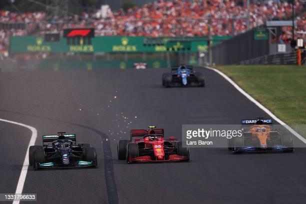 Lewis Hamilton of Great Britain driving the Mercedes AMG Petronas F1 Team Mercedes W12 overtakes Carlos Sainz of Spain driving the Scuderia Ferrari...