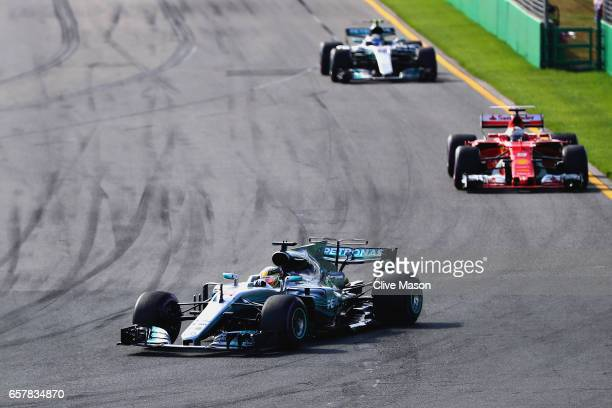 Lewis Hamilton of Great Britain driving the Mercedes AMG Petronas F1 Team Mercedes F1 WO8 leads Sebastian Vettel of Germany driving the Scuderia...