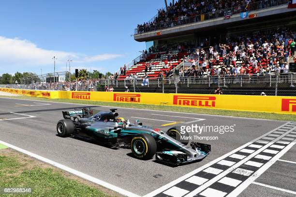 Lewis Hamilton of Great Britain driving the Mercedes AMG Petronas F1 Team Mercedes F1 WO8 crosses the line to take the win during the Spanish Formula...