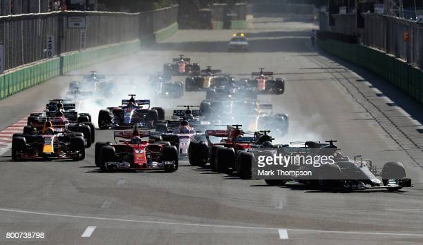 Lewis Hamilton of Great Britain driving the Mercedes AMG Petronas F1 Team Mercedes F1 WO8 leads the field into the first corner at the start during...