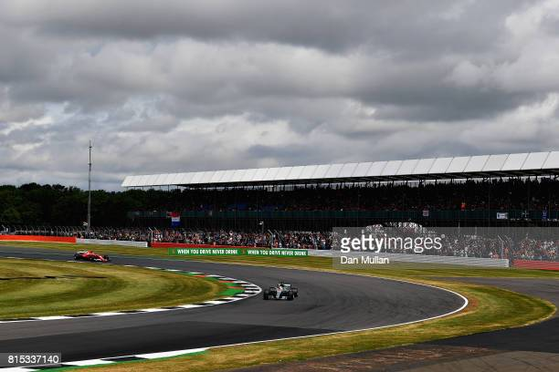 Lewis Hamilton of Great Britain driving the Mercedes AMG Petronas F1 Team Mercedes F1 WO8 leads Kimi Raikkonen of Finland driving the Scuderia...