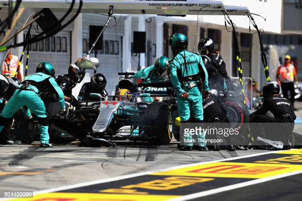 Lewis Hamilton of Great Britain driving the Mercedes AMG Petronas F1 Team Mercedes F1 WO8 makes a pit stop for new tyres during the Formula One Grand...