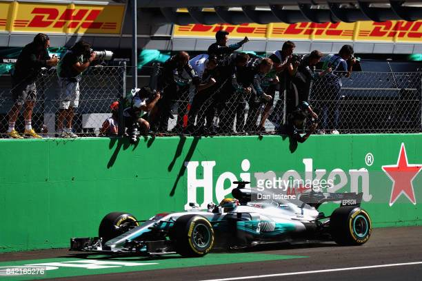 Lewis Hamilton of Great Britain driving the Mercedes AMG Petronas F1 Team Mercedes F1 WO8 crosses the line to take the win during the Formula One...