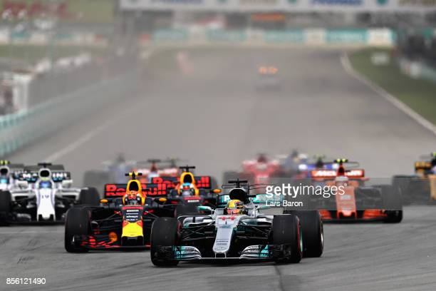 Lewis Hamilton of Great Britain driving the Mercedes AMG Petronas F1 Team Mercedes F1 WO8 leads the field into turn one at the start during the...