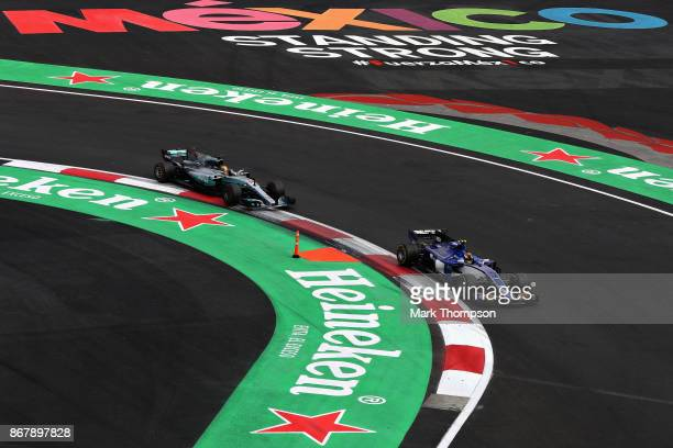 Lewis Hamilton of Great Britain driving the Mercedes AMG Petronas F1 Team Mercedes F1 WO8 chases down Pascal Wehrlein of Germany driving the Sauber...