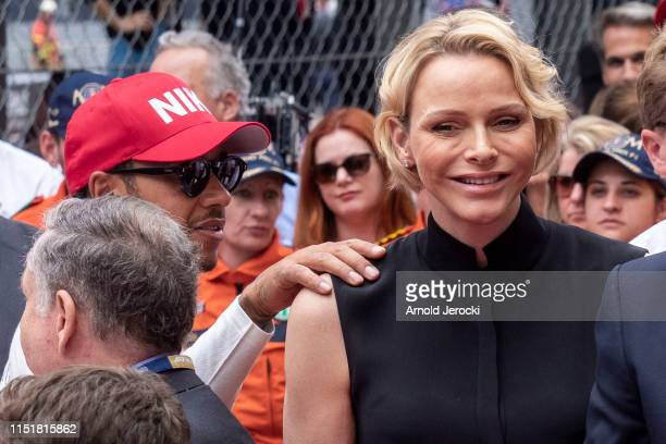 Lewis Hamilton places his hand on the shoulder of Princess Charlene of Monaco during a tribute to Niki Lauda during the F1 Grand Prix of Monaco on...