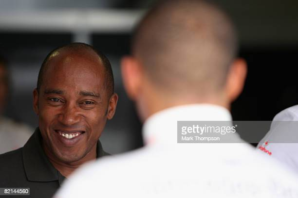 Lewis Hamilton's father Anthony Hamilton chats with his son in the pits during practice for the Hungarian Formula One Grand Prix at the Hungaroring...