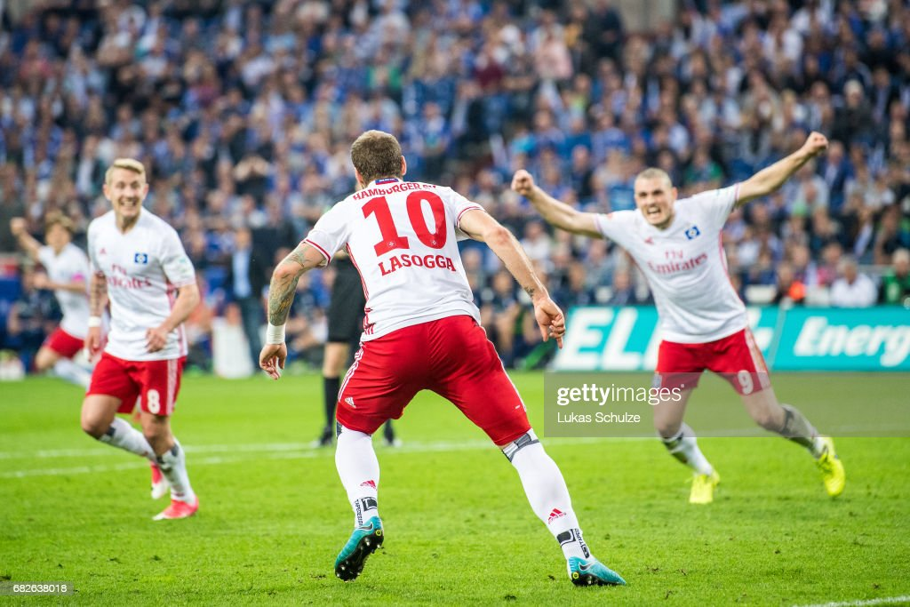 Lewis Holtby (L) and Kyriakos Papadopulos (R) of Hamburg celebrate the goal of Pierre-Michel Lasogga (C) of Hamburg during the Bundesliga match between FC Schalke 04 and Hamburger SV at Veltins-Arena on May 13, 2017 in Gelsenkirchen, Germany.