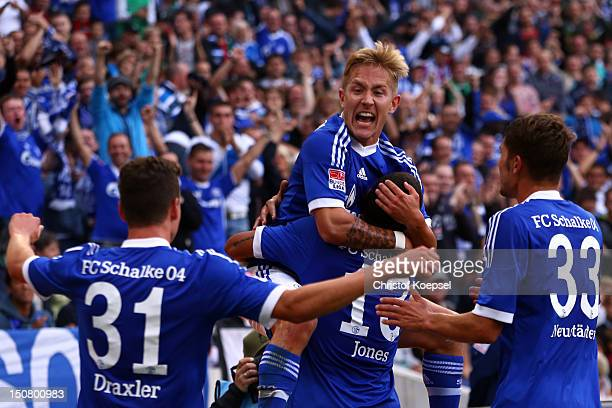 Lewis Holtby celebrates the second goal with Julian Draxler Jermaine Jones and Roman Neustaedter of Schalke during the Bundesliga match between...