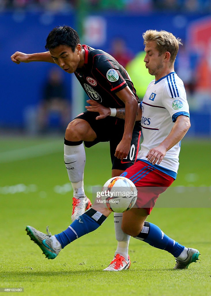 Lewis Holtby (R) of Hamburg and Makoto Hasebe of Frankfurt battle for the ball during the Bundesliga match between Hamburger SV and Eintracht Frankfurt at Volksparkstadion on September 19, 2015 in Hamburg, Germany.