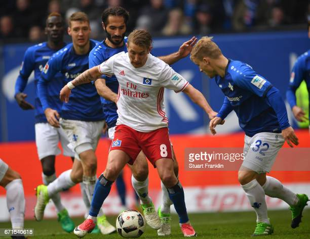 Lewis Holtby of Hamburg is challenged by Fabian Holland and Hamit Altintop of Darmstadt during the Bundesliga match between Hamburger SV and SV...