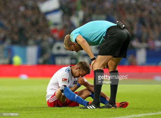 Lewis Holtby of Hamburger SV on the ground and referee Arne Aarnink looks on during the Second Bundesliga match between Hamburger SV and DSC Arminia...