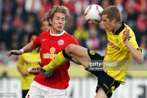 Lewis Holtby of Mainz is challenged by Sven Bender of Dortmund during the Bundesliga match between FSV Mainz 05 and Borussia Dortmund at the Bruchweg...