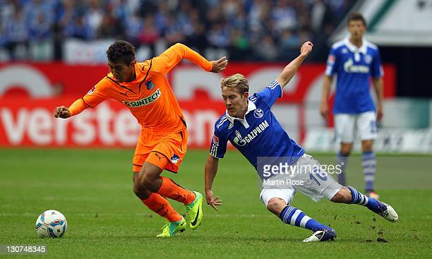 Lewis Holtby of Schalke and Roberto Firmino of Hoffenheim battle for the ball during the Bundesliga match between FC Schalke 04 and 1899 Hoffenheim...