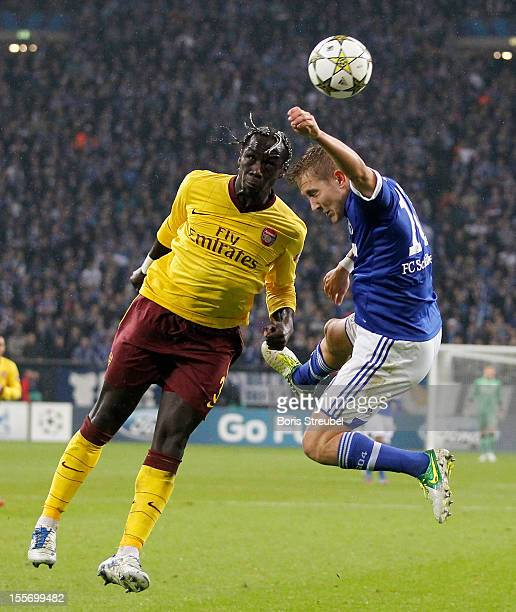 Lewis Holtby of Schalke jumps for a header with Bacary Sagna of Arsenal during the UEFA Champions League group B match between FC Schalke 04 and...