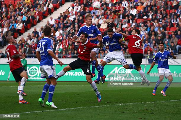 Lewis Holtby of Schalke scores the second goal against Mario Eggimann of Hannover and Steven Cherundolo of Hannover during the Bundesliga match...