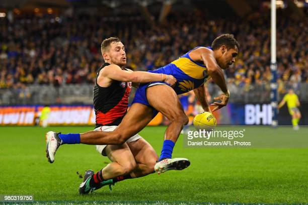 Lewis Jetta of the Eagles is tackled by Devon Smith of the Bombers during the 2018 AFL round 14 match between the West Coast Eagles and the Essendon...