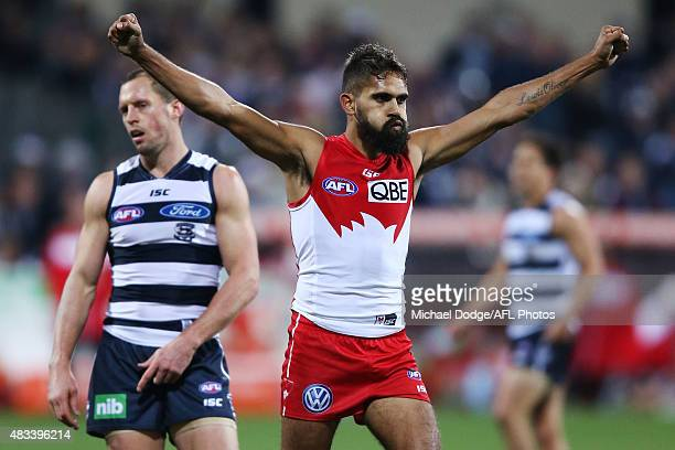 Lewis Jetta of the Swans celebrates a goal in front of James Kelly of the Cats during the round 19 AFL match between the Geelong Cats and the Sydney...