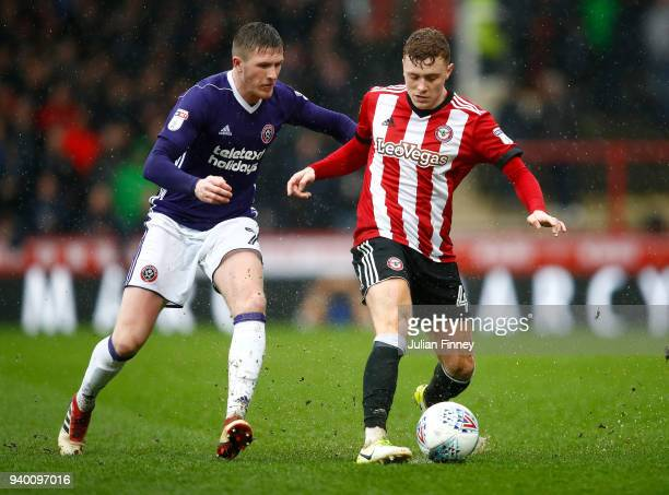 Lewis Macleod of Brentford battles with John Lundstram of Sheffield United during the Sky Bet Championship match between Brentford and Sheffield...