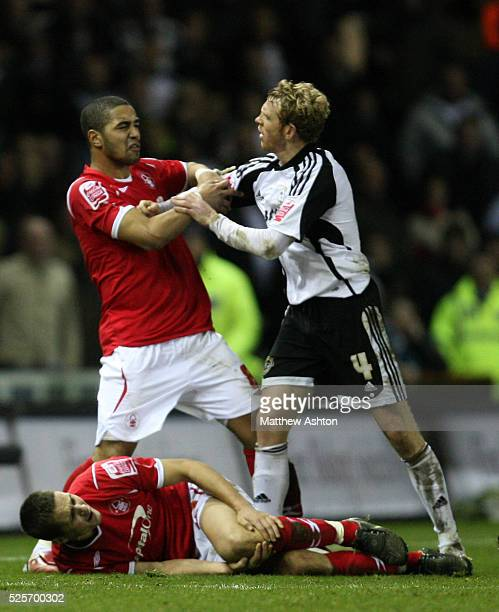 Lewis McGugan of Nottingham Forest and Paul Green of Derby County clash as Chris Cohen of Nottingham Forest lies injured on the pitch