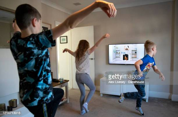 Lewis Mia and Asa who are the photographer's children take part in a live streamed broadcast PE session with fitness trainer Joe Wicks on March 25...