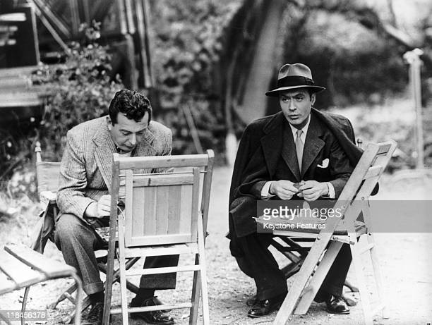 Lewis Milestone Russianborn film director sitting alongside French actor Charles Boyer using chairs for tables as they take lunch during a break in...