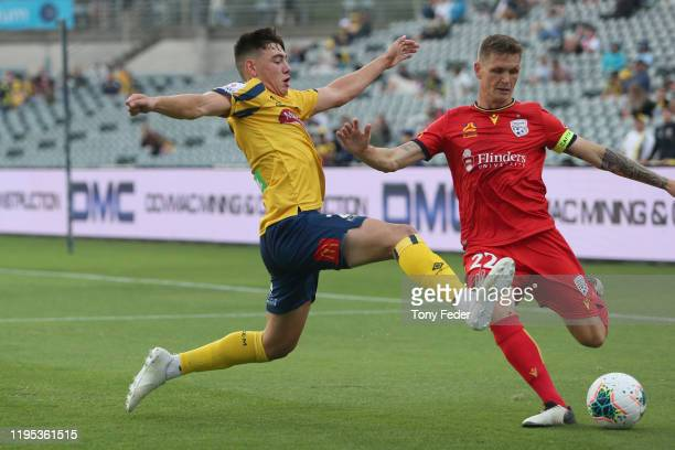 Lewis Miller of the Central Coast Mariners contests the ball with Michael Jakobsen of Adelaide United during the round 11 ALeague match between the...