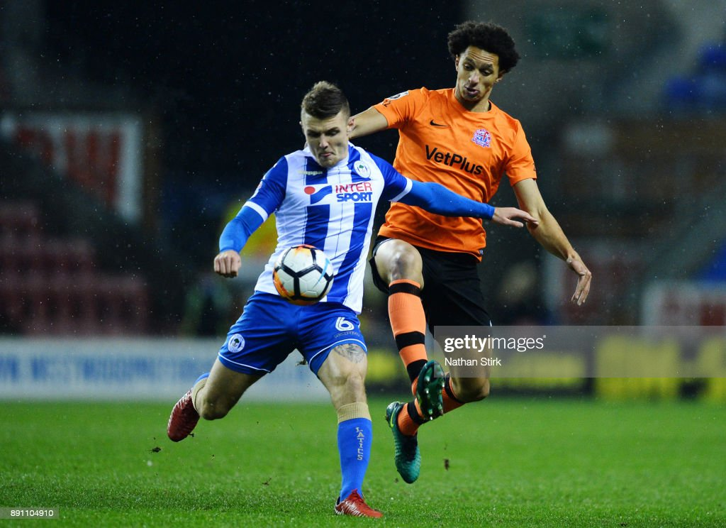 Lewis Montrose of AFC Fylde and Max Power of Wigan Athletic in action during The Emirates FA Cup Second Round Replay match between Wigan Athletic and AFC Fylde at the DW Stadium on December 12, 2017 in Wigan, England.