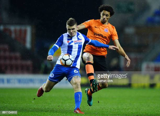 Lewis Montrose of AFC Fylde and Max Power of Wigan Athletic in action during The Emirates FA Cup Second Round Replay match between Wigan Athletic and...