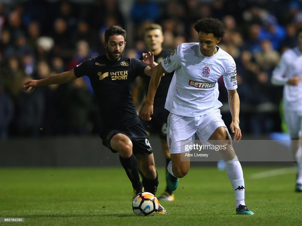 Lewis Montrose of AFC Fylde beats Will Grigg of Wigan Athletic during The Emirates FA Cup Second Round between AFC Fylde and Wigan Athletic on December 1, 2017 in Kirkham, England.