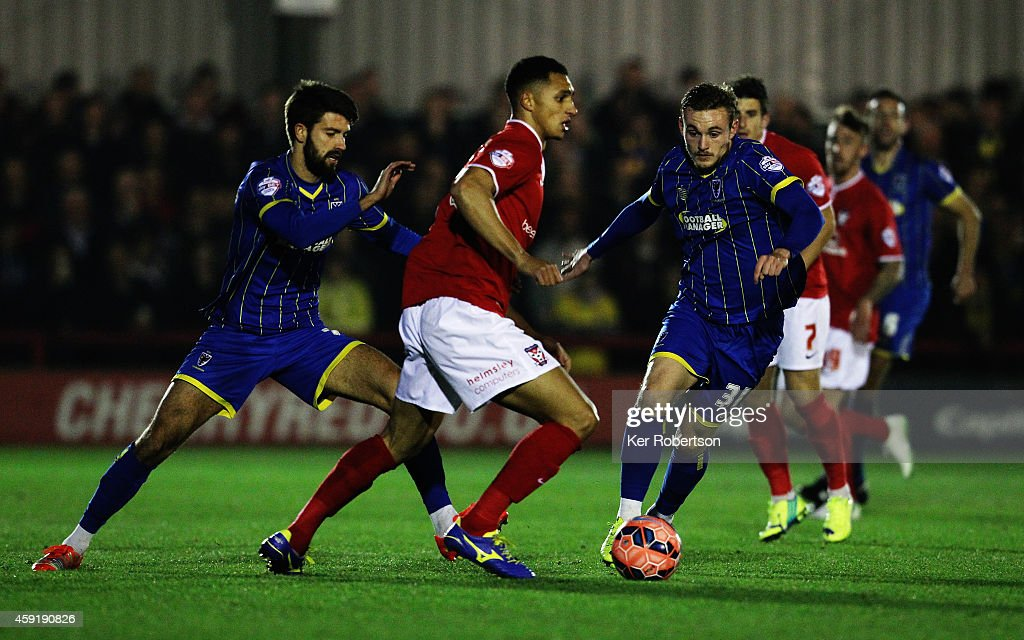 Lewis Montrose (C) of York City holds off the challenge of George Francomb (L) and Frankie Sutherland (R) of AFC Wimbledon during the FA Cup First Round Replay between AFC Wimbledon and York City at The Cherry Red Records Stadium on November 18, 2014 in Kingston upon Thames, England.