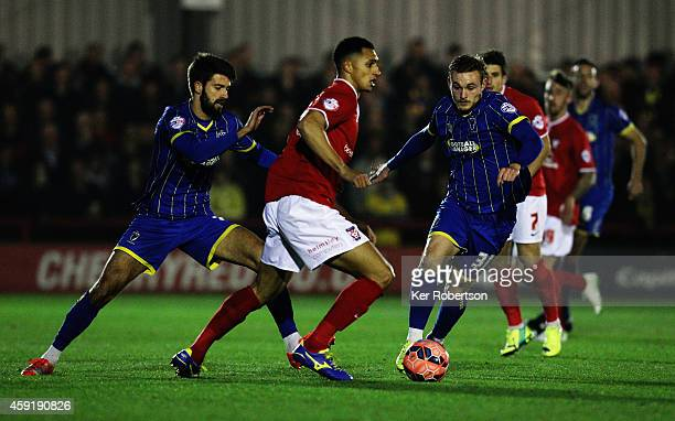 Lewis Montrose of York City holds off the challenge of George Francomb and Frankie Sutherland of AFC Wimbledon during the FA Cup First Round Replay...