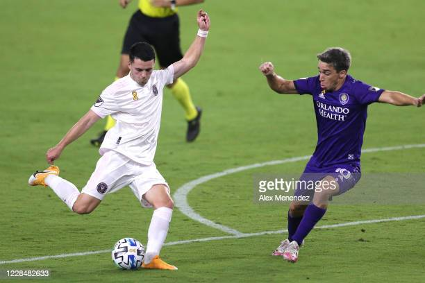 Lewis Morgan of Inter Miami CF kicks the ball in front of Mauricio Pereyra of Orlando City SC during an MLS soccer match at Exploria Stadium on...