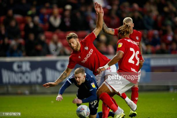 Lewis O'Brien of Huddersfield Town goes down in the penalty box under pressure from Ashley Williams Nathan Baker and Jack Hunt of Bristol City during...