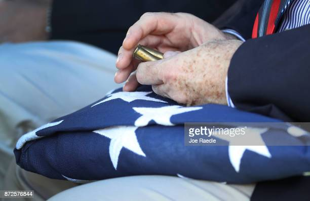 Lewis Sowell Jr the nephew of US Army Sergeant Richard 'Tiny' Sowell holds a folded American flag plus the shell casing from the twentyone gun salute...