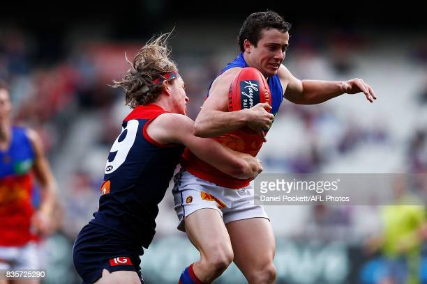 Lewis Taylor of the Lions and Jayden Hunt of the Demons contest the ball during the round 22 AFL match between the Melbourne Demons and the Brisbane...
