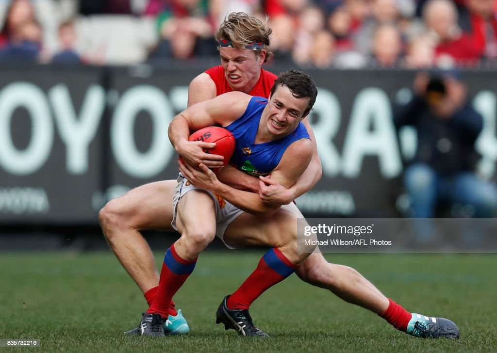 Lewis Taylor of the Lions is tackled by Jayden Hunt of the Demons during the 2017 AFL round 22 match between the Melbourne Demons and the Brisbane Lions at the Melbourne Cricket Ground on August 20, 2017 in Melbourne, Australia.