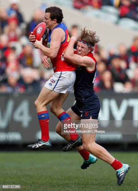 Lewis Taylor of the Lions is tackled by Jayden Hunt of the Demons during the 2017 AFL round 22 match between the Melbourne Demons and the Brisbane...
