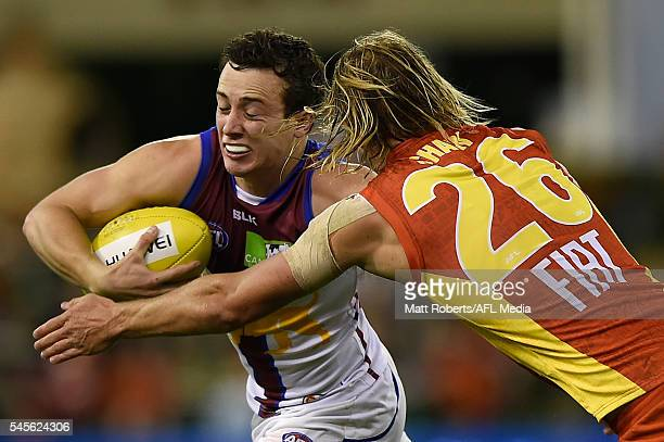 Lewis Taylor of the Lions is tackled during the round 16 AFL match between the Gold Coast Suns and the Brisbane Lions at Metricon Stadium on July 9...