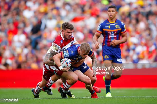 Lewis Tierney of Catalans Dragons is tackled by Oliver Gildart of Wigan Warriors during the Betfred Super League match at Camp Nou on May 18 2019 in...