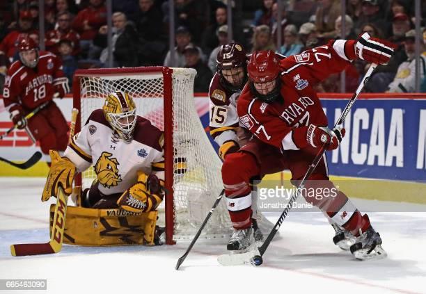 Lewis ZerterGossage of the Harvard Crimson tries to get off a shot against Hunter Miska of the MinnesotaDuluth Bulldogs as Willie Raskob defends...