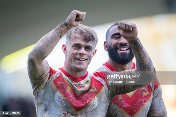 LewisTierney of Catalans Dragons and SamisoniLangi of Catalans Dragons salute the fans as they celebrate the team upset victory during the Catalans...